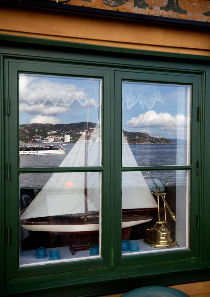 Sørgmodig modellseilbåt er nødt til å se kanalbåter leke på fjorden mens den selv må stå til utstilling på Nordnes. Foto: Bjørn Erik Larsen/Bergens Tidende